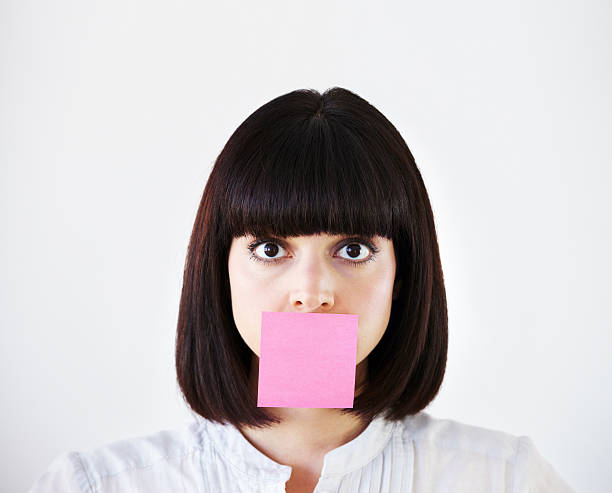Stress is stifling her creative voice Conceptual image of a young businesswoman with a pink post-it note covering her mouth finger on lips stock pictures, royalty-free photos & images