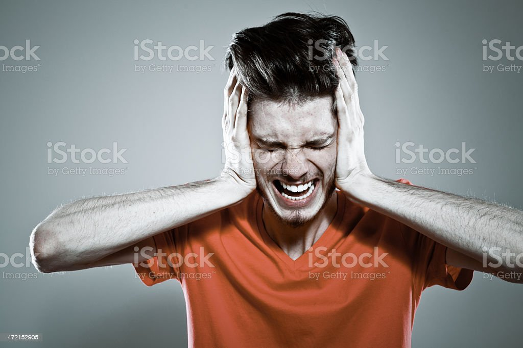 Stress Portrait of scared young man screaming. Studio shot. 20-29 Years Stock Photo