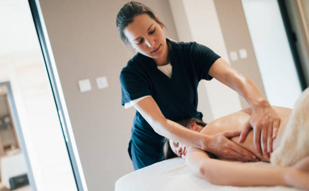 stress relieving massage by young smart therapist - massage therapist stock pictures, royalty-free photos & images
