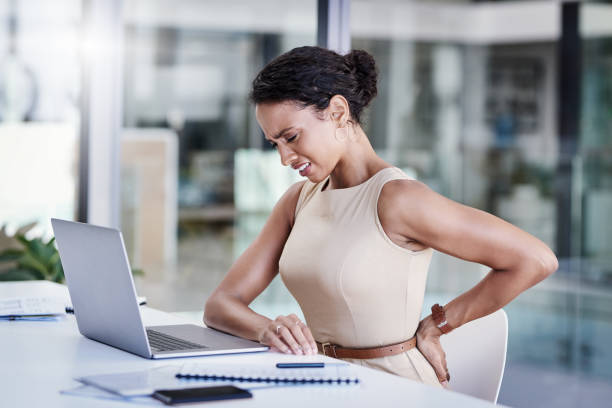 Stress, the career destroyer Shot of a young businesswoman experiencing back pain while working in a modern office back pain stock pictures, royalty-free photos & images