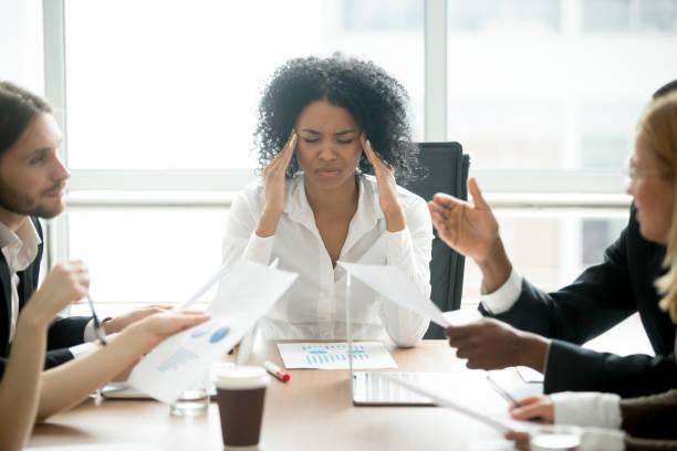 betonade afrikanska affärskvinna trött eller lider av huvudvärk vid möte - work stress bildbanksfoton och bilder