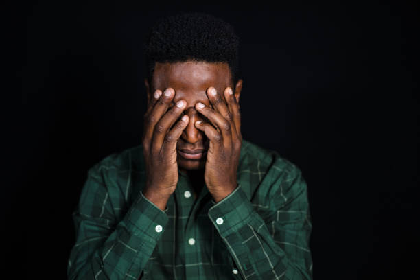 Stressed african man on black background Portrait of african man with hand covering face and thinking. Male in checkered shirt looking worried on black background. head in hands stock pictures, royalty-free photos & images