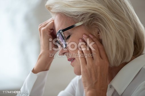 Close up of stressed senior businesswoman in glasses touch head suffering from strong headache or migraine, aged grey-haired woman worker wearing spectacles feel unhealthy having health problems
