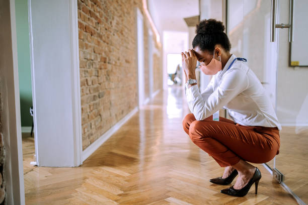 Stressed and overworked businesswoman crouching in the office hallway stock photo