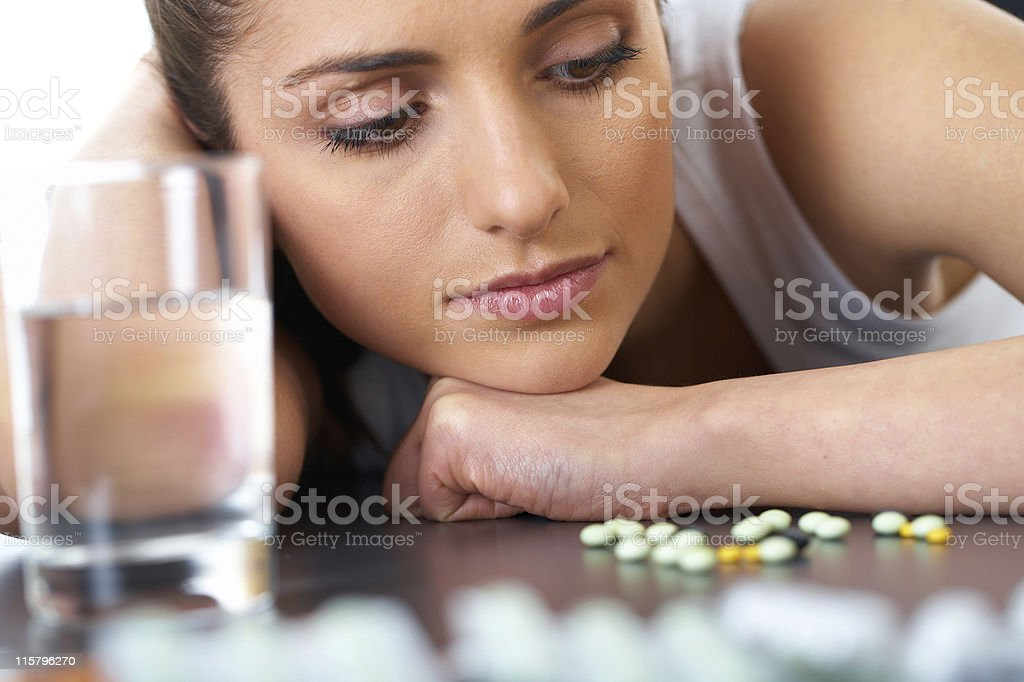 stressed and sad brunette with some pills, glass of water royalty-free stock photo