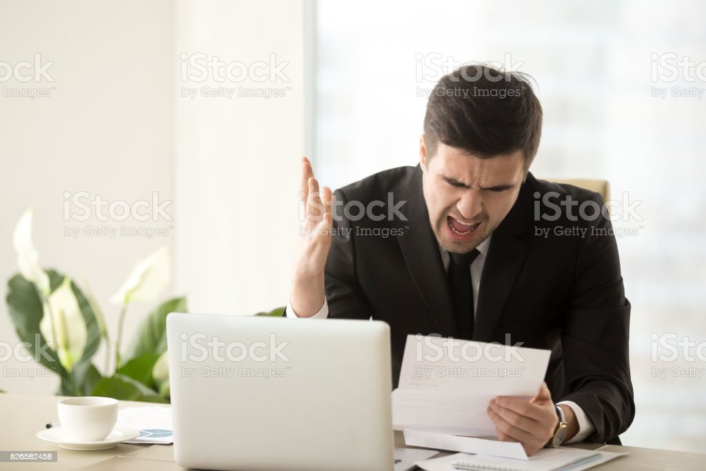 Stressed angry businessman shouting dissatisfied with bad document, debt charges stock photo