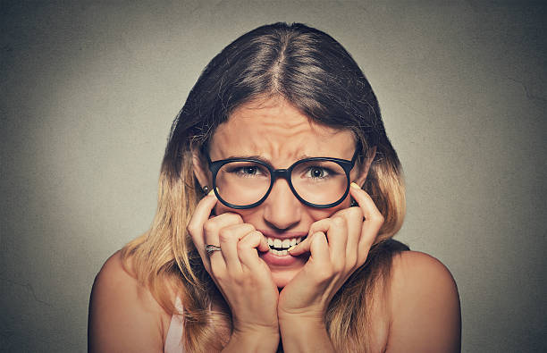 stressed anxious woman in glasses biting fingernails - fear stock photos and pictures
