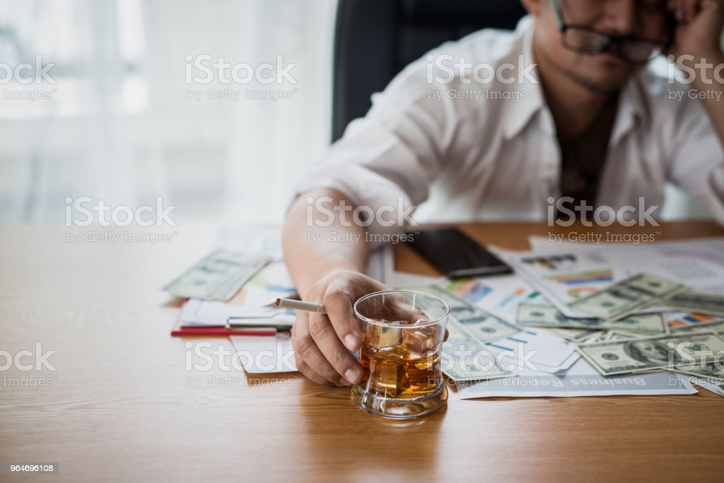 Stressed asian businessman holding a glass of whiskey and smoking. he sleep on the money, data charts, business document at office desk.  alcohol addiction - drunk businessman concept royalty-free stock photo