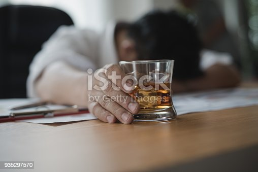 istock Stressed asian businessman holding a glass of whiskey he sleeping and Data Charts,business document at office desk.  alcohol addiction - drunk businessman concept 935297570