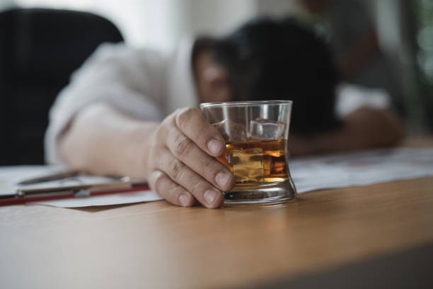 stressed asian businessman holding a glass of whiskey he sleeping and data charts,business document at office desk.  alcohol addiction - drunk businessman concept - dipsomania stock pictures, royalty-free photos & images