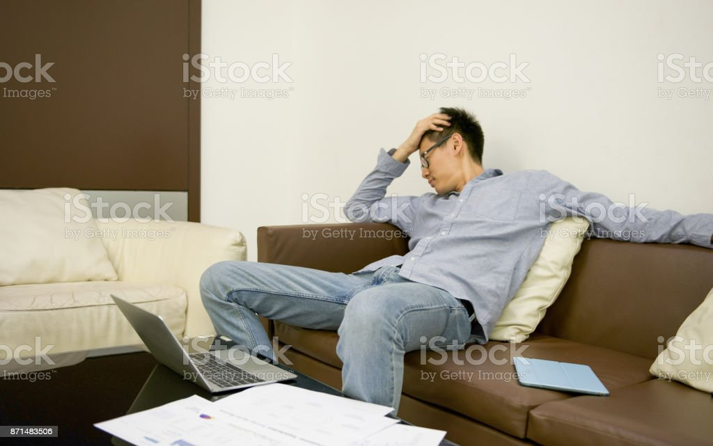 Stressed Asian businessman using a smartphone in living room at night stock photo