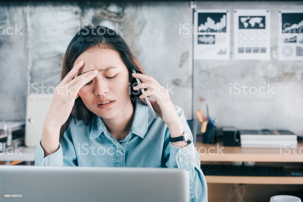 Stressed Asian creative designer woman cover her face with hand and feel upset while talk on mobile phone with customer in front of laptop computer on desk at office,Stress office lifestyle concept stock photo