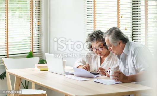 istock Stressed Asian Senior Couple using calculator and calculate family budget, Debts, monthly expenses in home during Financial economic crisis. Senior man and woman looking at account book, bill, passbook, receipt and laptop computer on table 1222713269