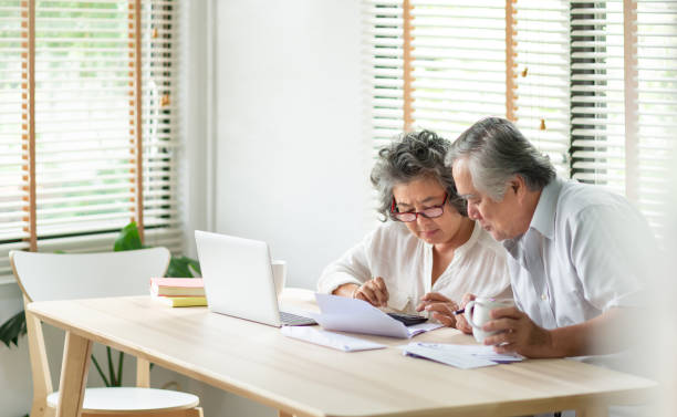 Stressed Asian Senior Couple using calculator and calculate family budget, Debts, monthly expenses in home during Financial economic crisis. Senior man and woman looking at account book, bill, passbook, receipt and laptop computer on table stock photo