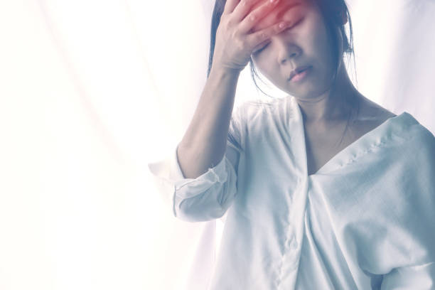 stressed Asian woman having headache and feeling dizzy from migraine stock photo