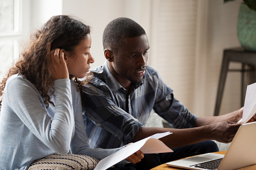 Stressed Black Couple With Bills And Laptop At Home Stock Photo - Download Image Now