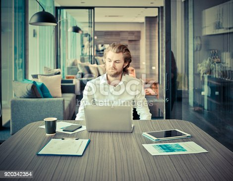 840623374 istock photo Stressed blonde business man using a laptop in living room at night 920342354