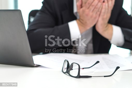 istock Stressed business man covering face with hands in office. Working over time or too much. Problem with failing business or confusion with crisis. Entrepreneur in bankruptcy. Burnout and overwork. 852477948