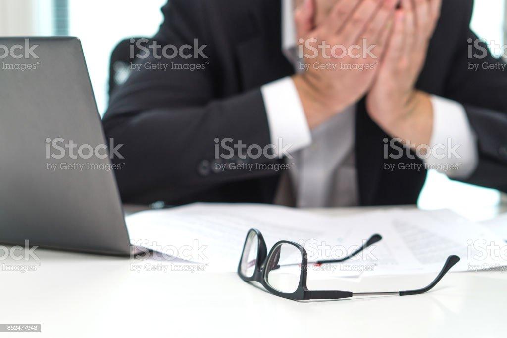 Destaca el hombre de negocios que cubre la cara con las manos en la oficina. Trabajar sobre tiempo o demasiado. Problema con no negocio o confusión con crisis. Empresario en quiebra. Agotamiento y exceso de trabajo. - foto de stock
