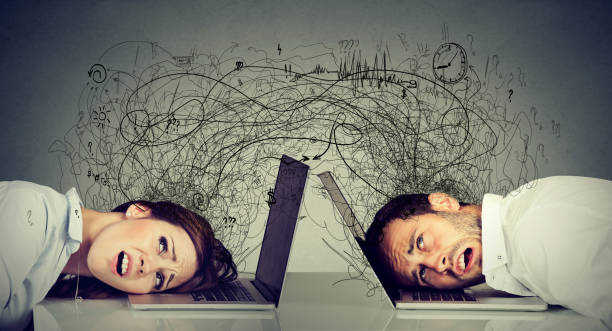 Stressed business woman and man resting head on laptop sitting at table frustrated with each other exchanging with clutter of negative thoughts and emotions. Distant relationship concept stock photo