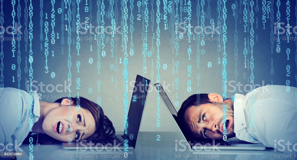 Stressed business woman and man resting head on laptop under binary code rain sitting at table frustrated with each other stock photo