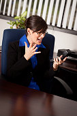Color photo of a young business woman stressed out in her office screaming at her phone.