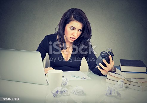 840623374 istock photo Stressed business woman sitting at her office desk pressured by lack of time 839871364