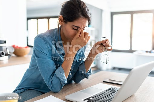 Shot of stressed business woman working from home on laptop looking worried, tired and overwhelmed.