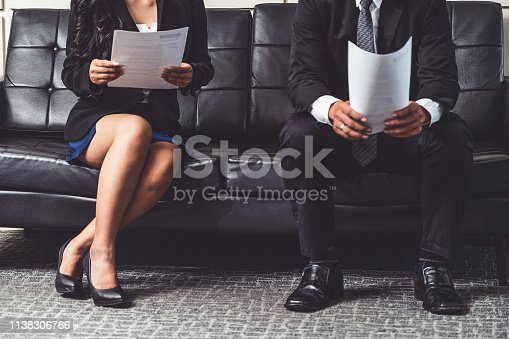 Stressed businessman and businesswoman candidate sit and wait for interview at the company office. Job application, business recruitment and Asian labor hiring concept.