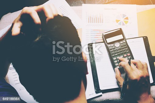 istock Stressed businessman and graph doing finance with calculate about cost. 649188564