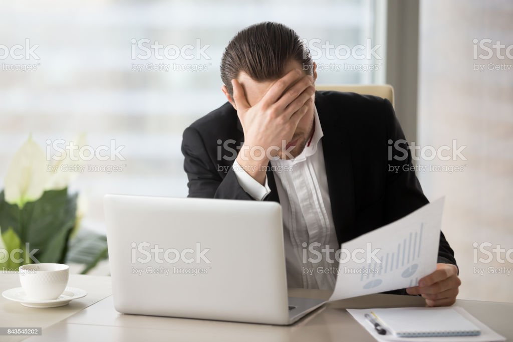 Stressed businessman facepalming because of failing financial report statistics. stock photo