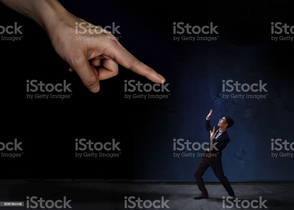 Stressed Businessman in Under Pressured Concept, Small Worker Scared a Huge Pointing Hand stock photo