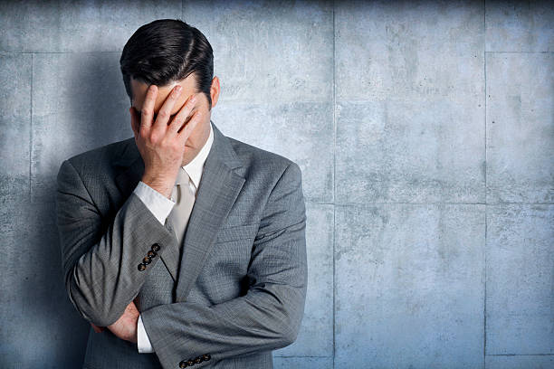 Stressed businessman leaning against concrete wall A stressed businessman places his head in his hands as he leans up against a concrete wall.  Photographed from the waist up, the businessman is placed on the left side of image.  There is ample room for text in the negative space created on the right side of image. head in hands stock pictures, royalty-free photos & images