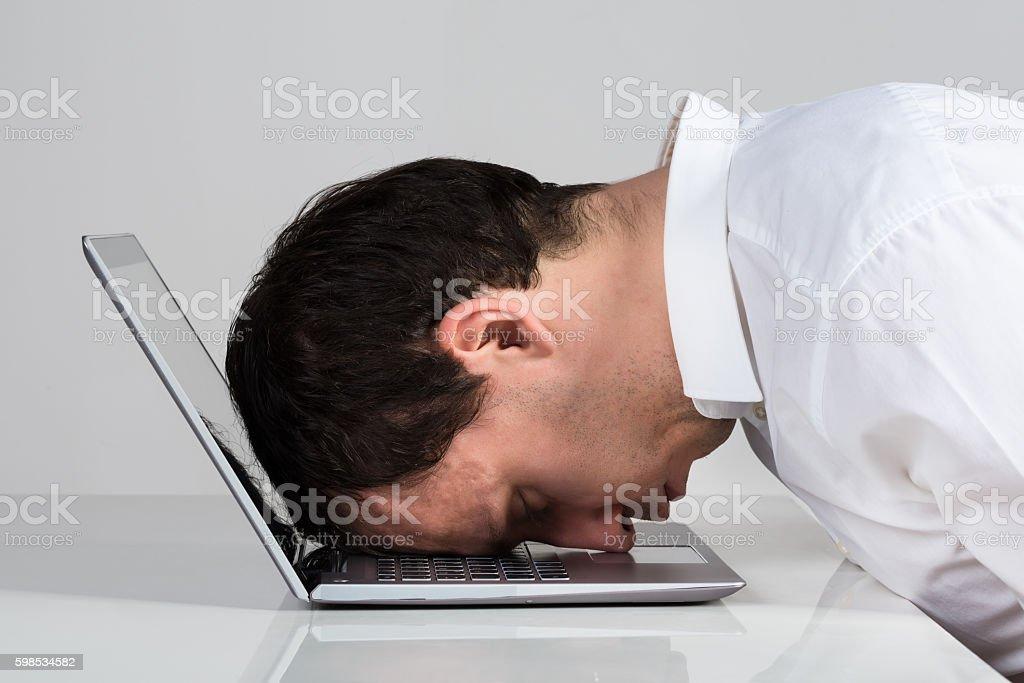 Stressed Businessman Leaning On Laptop At Desk photo libre de droits