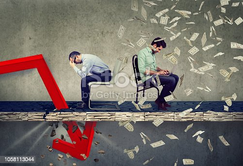 Stressed desperate businessman looking down at falling down red arrow sitting next to a successful smart guy working on laptop computer under money rain