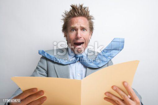 481644192 istock photo Stressed Businessman Office Worker Opening Manila Folder of Dread 173692870