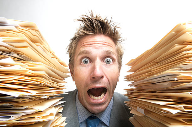 Stressed Businessman Office Worker Screaming for Help Between File Folders stock photo