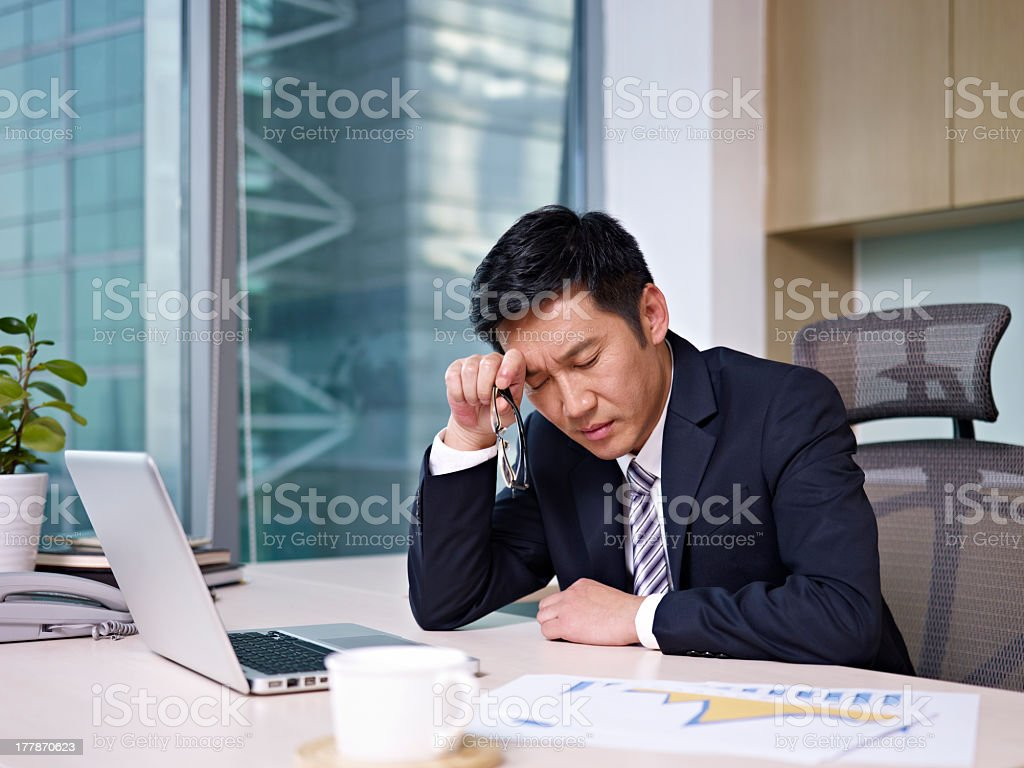 Stressed businessman rubbing head looking at charts stock photo