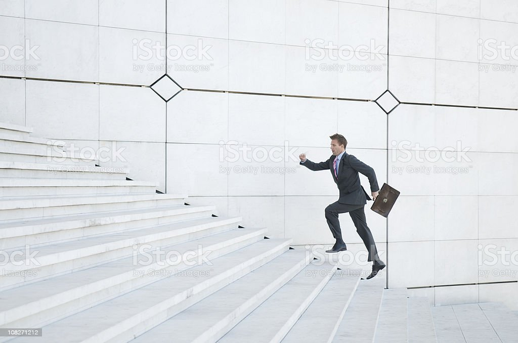 Stressed Businessman Running Up White Staircase Outdoors stock photo