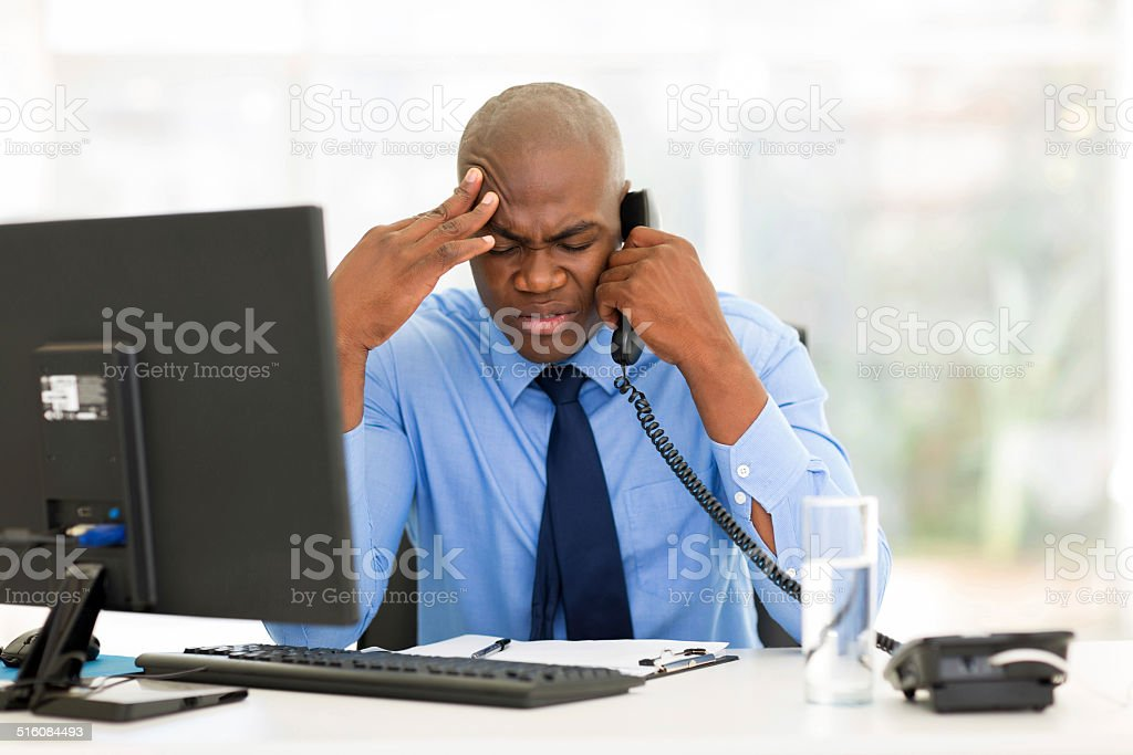 stressed businessman talking on landline phone stock photo