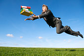 Stressed businessman tripping above green meadow to catch his flying file folders