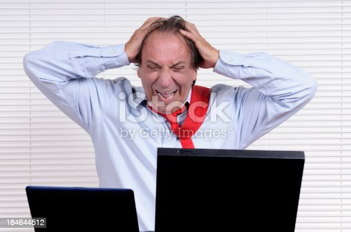 929420656 istock photo Stressed Businessman with Head in Hands Looking PC 184644512