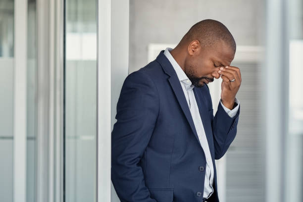 Stressed businessman with headache standing Stressed mature business man rubbing eyes standing in office. African american businessman in formal clothing feeling tired rubbing nose and eyes, for fatigue and headache. Depressed and anxious man in office feeling frustrated after layoff. downsizing unemployment stock pictures, royalty-free photos & images