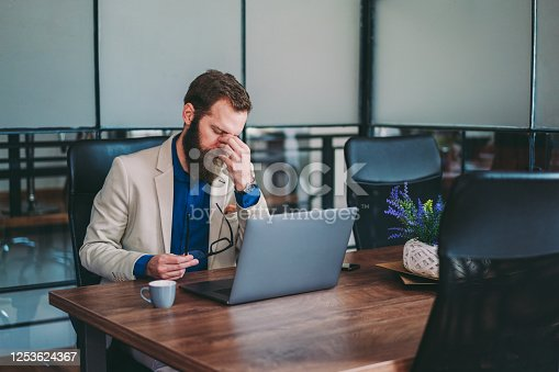 913327640 istock photo Stressed businessman working late in the office 1253624367