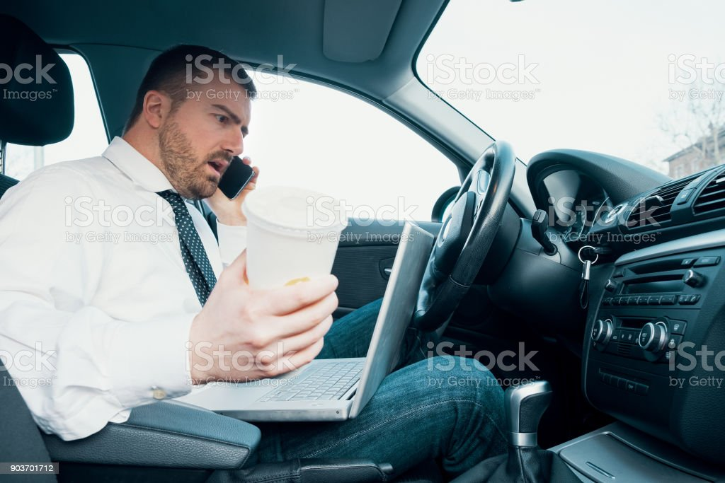 Stressed businessman working seated in car stock photo
