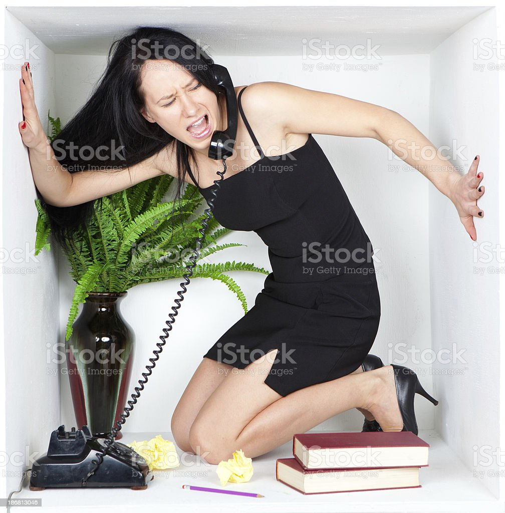 Stressed businesswoman screaming into phone inside small office cubicle stock photo