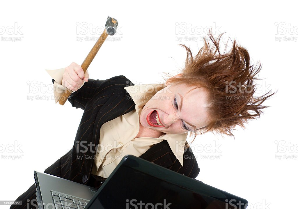 stressed businesswoman smashing her laptop with a hammer royalty-free stock photo