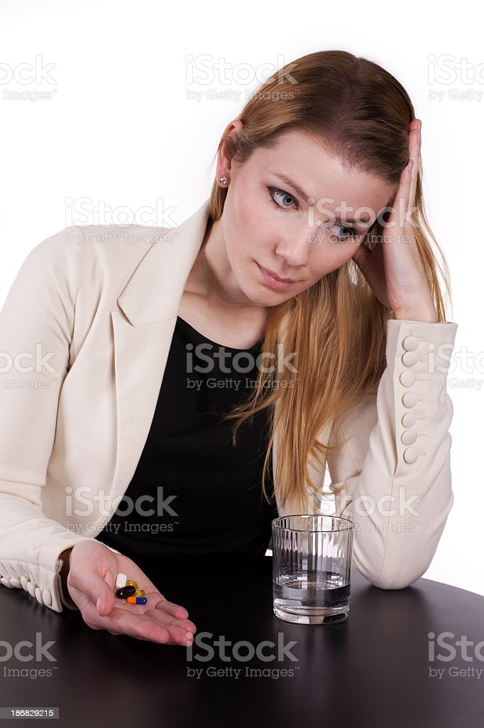 Stressed businesswoman with handful of pills royalty-free stock photo