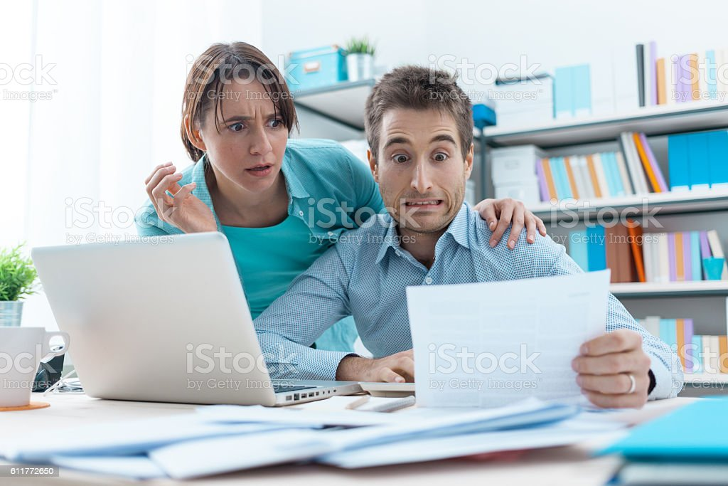 Stressed couple checking bills - Foto de stock de Abrazar libre de derechos
