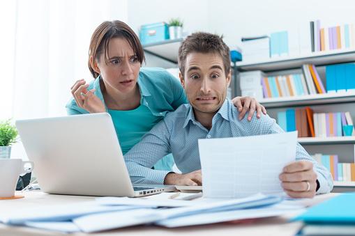 Stressed Couple Checking Bills Foto de stock y más banco de imágenes de Abrazar